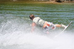Making a Move. Teenage boy performing a move on the wakeboard royalty free stock photography