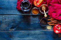 Making mulled wine. Dark rustic background with colorful ingredients for making mulled wine. Wine in glass bottle, honey, apples and spices with old wooden spoon Stock Photos