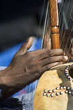 Making Music. Black hand playing a native stringed instrument Royalty Free Stock Photos