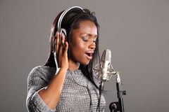 Making music beautiful black woman singing in mic. Beautiful young african american woman with eyes closed, wearing headphones and singing into microphone in royalty free stock photos
