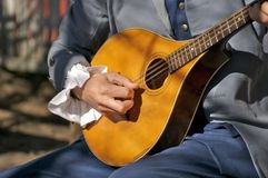 Making Music III. Strolling troubadour playing vintage guitar stock image