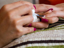 Making nails. Closeup of a woman& x27;s hand painting the nails of another one royalty free stock photos