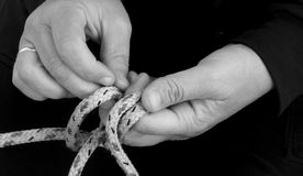 Making a knot. The making of a nautical knot stock photography