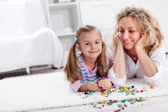 Making a necklace for mom - little girl playing. With wooden beads and pearls Royalty Free Stock Photo