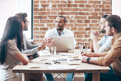 Making new strategy. Group of young people discussing something while sitting at the wooden table in the office stock image