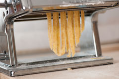 Making noodles with pasta machine from homemade spelt dough. Stock Photography