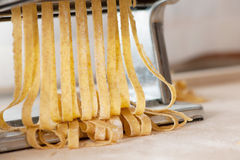 Making noodles with pasta machine from homemade spelt dough. Royalty Free Stock Photo
