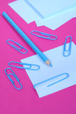 Making Notes. Blank paper notes, paper clips and a blue pencil, on pink surface Stock Image