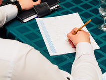 Making notes. Close-up of man in formalwear writing something. In his note pad Stock Images