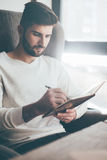 Making notes. Confident young man writing something in notebook while sitting at his working place in office Stock Image