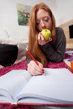 Making notes and eating apple Stock Photos