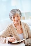 Making notes. Portrait of aged female with notepad looking at camera with smile Stock Photography