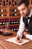 Making notes about wine. Royalty Free Stock Image