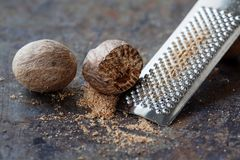 Making nutmeg powder process. Nuts silver grater. Kitchen still life photo. Shallow depth of field, aged brown rusty Stock Photos