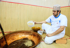 Making of Omani halwa. NIZWA, OMAN, MAY 27, 2016: factory worker adding ingredients to a kettle for making of traditional Omani halwa Stock Photography
