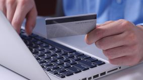 Making online bank transfers, man's hand holds a credit card while entering data in laptop. Close up. Man shopping online by smartphone and payment by credit stock footage