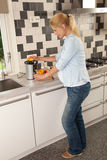 Making orange juice. Attractive pregnant woman making orange juice for herself Royalty Free Stock Images