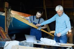 Making paddle. Senior and young shipbuilding engineers working over wooden paddle for boat or other vessel in workshop royalty free stock images