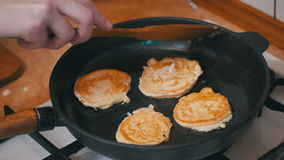 Making Pancake, Crepes, Flapjack on Frying Pan in a Domestic Kitchen. The Dough Falls on the Hot Skillet. Cooking Pancakes in a Domestic Kitchen. Cooking food at stock footage