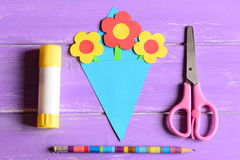 Making paper crafts for mother`s day or birthday. Step. Paper flowers bouquet, scissors, glue stick, pencil on a wooden table Stock Photos
