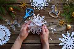 Making paper snowflakes with your own hands. Children& x27;s DIY. Merry Christmas and New Year concept. Step 3. Open the snowflake.  royalty free stock photo