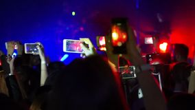 Making party at a rock concert and hold smartphone cameras with digital displays stock video