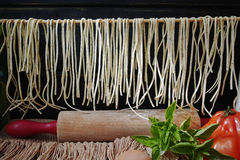 Making of pasta spaghetti with basil. Homemade pasta spaghetti on black wooden background with flour, eggs, basil and tomatoes Royalty Free Stock Photography