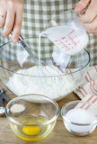 Making pastry dough. A baker adds a milk into the flour. Ingredients for baking in bowls Royalty Free Stock Photo