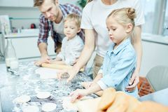 Making pastry. Modern family of four kneading and rolling dough together while cooking homemade pastry in the kitchen Royalty Free Stock Image