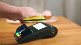 Making a payment in cafe with NFC technology on credit card stock video footage