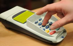 Making payment using credit plastic card reader. Woman's hand dialing pin on plastic credit card reader in a shop while paying Royalty Free Stock Image