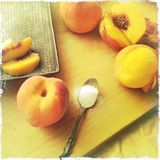 Making peach cobbler. Fresh peaches peeled, cut and whole with a vintage pan and spoonful of sugar royalty free stock images