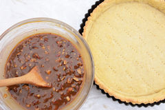 Making pecan pie - nutty pie filling and pie crust. Making pecan pie - nutty pie filling ready to pour into the blind-baked pie crust Stock Photo