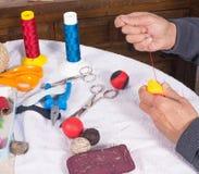 Making pelota balls. Expert hands crafting  leather balls for traditional pelota sport Stock Photo