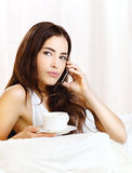 Making phone call and holding coffee in bed Royalty Free Stock Photos