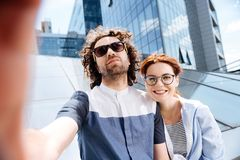 Handsome curly man making photo with his appealing woman. Making photo. Handsome curly men feeling loved and relaxed while making photo with his appealing woman royalty free stock photos