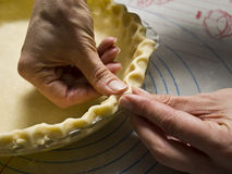Making a Pie Crust. A bakers shapes dough into a homemade pie crust stock photography