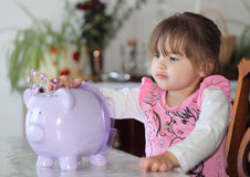 Making a Piggy Bank Deposit. Cute toddler girl putting money her piggy bank Stock Images
