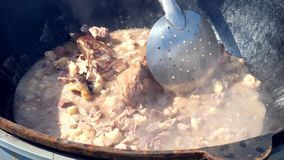 Making pilaf outdoor on open fire in cauldron. Mixes fatty meat.  stock video footage