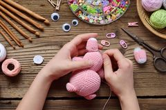 Making pink pig. Crochet toy for child. On table threads, needles, hook, cotton yarn. Step 2 - to sew all details of toy. Handmade. Crafts. DIY concept. Small royalty free stock photography