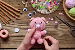 Free Making Pink Pig. Crochet Toy For Child. On Table Threads, Needles, Hook, Cotton Yarn. Step 2 - To Sew All Details Of Toy. Handmade Stock Image - 132129151