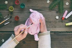 Making Pink pig, symbol of 2019. Painting clay toy with gouache. Creative leisure for children. Handmade crafts on holiday with. Your own hands. DIY project royalty free stock image