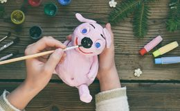Making Pink pig, symbol of 2019. Painting clay toy with gouache. Creative leisure for children. Handmade crafts on holiday with. Your own hands. DIY project stock photography