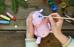 Making Pink pig, symbol of 2019. Painting clay toy with gouache. Creative leisure for children. Handmade crafts on holiday with. Your own hands. DIY project stock photos