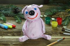 Making Pink pig, symbol of 2019. Painting clay toy with gouache. Creative leisure for children. Handmade crafts on holiday with royalty free stock photo