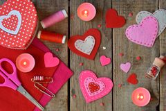 Making pink and red hearts of felt with your own hands. Valentine`s Day background. Valentine gift making, diy hobby. Children`s stock photos