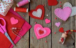 Making pink and red hearts of felt with your own hands. Valentine`s Day background. Valentine gift making, diy hobby. Children`s. Making pink and red hearts of stock photo