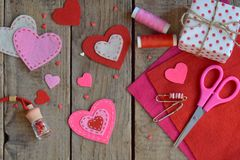 Making pink and red hearts of felt with your own hands. Valentines Day background. Valentine gift making, hobby. Childrens DIY con royalty free stock image