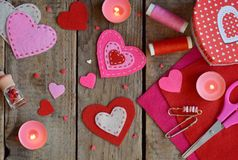 Making pink and red hearts of felt with your own hands. Valentines Day background. Valentine gift making, hobby. Childrens DIY stock photos