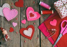 Making pink and red hearts of felt with your own hands. Valentines Day background. Valentine gift making, hobby. Childrens DIY royalty free stock photos